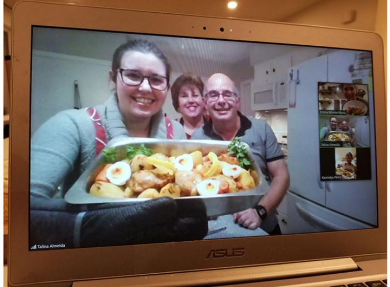 Laptop screen shows family displaying food they made.