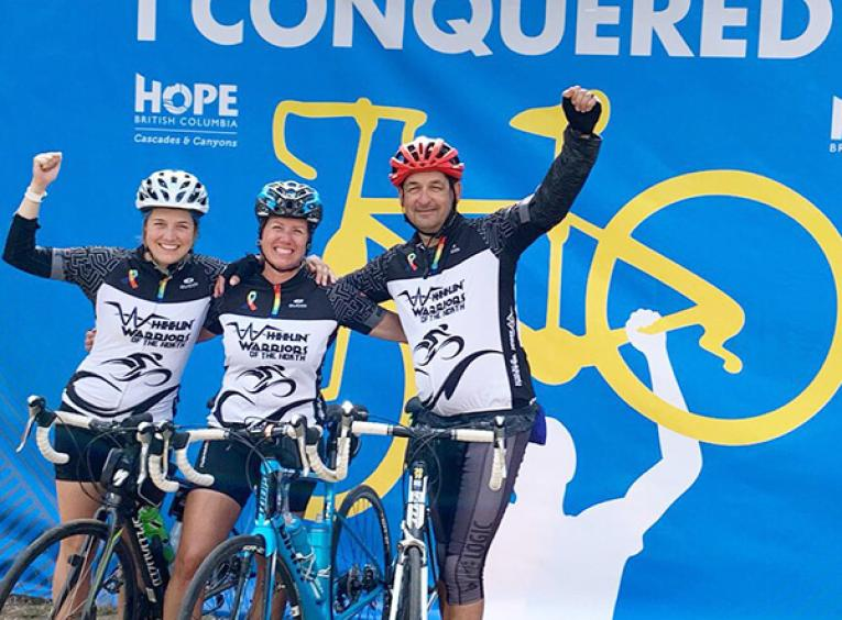 Haylee, her mom, and dad celebrate finishing the 2019 Ride to Conquer Cancer in their bike outfits with helmets on, and arms raised.