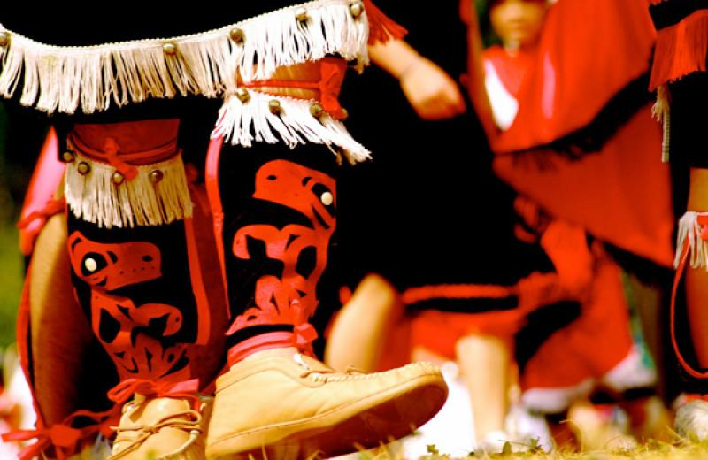 A person's legs are in the foreground, wearing moccasins, and traditional leggings. More similarly dressed people are blurred in the background.