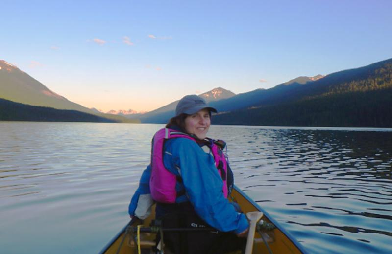 Ibolya is in the front of a canoe on a clam lake, surrounded by mountains.