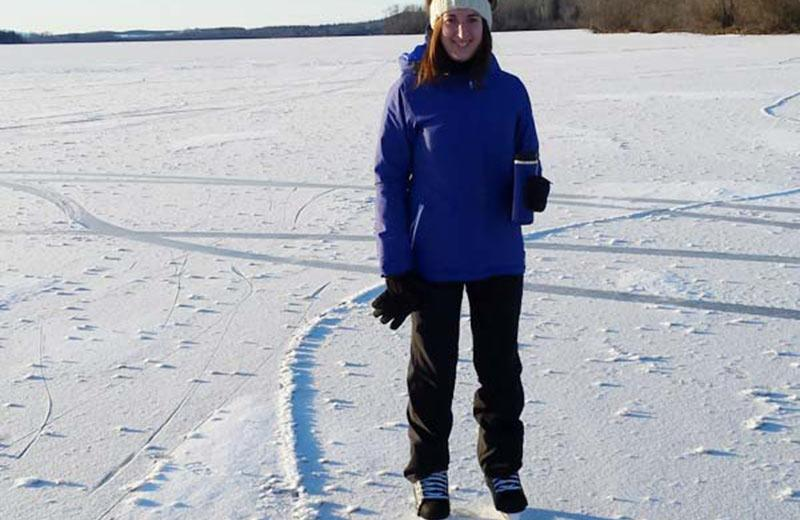 Woman standing on a frozen lake with ice skates on.