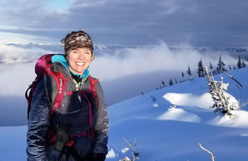 Tanya Carter is pictured on top of a mountain in the snow. In the distance is a snowy mountain range.