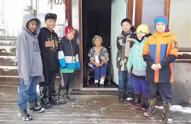 Group of kids and elder standing outside on a house deck in winter.