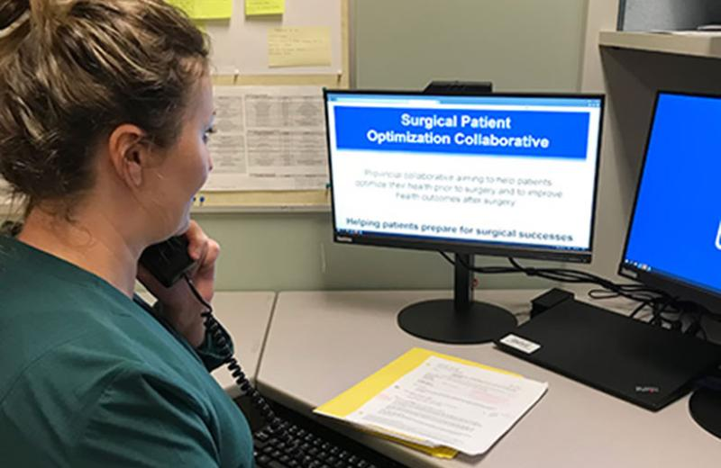 "A side angle shot of a woman in a green sweater sitting at a desk in front of a computer screen that says ""Surgical Patient Optimization Collaborative."""