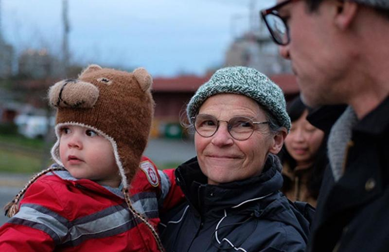 A woman outside holding a toddler boy in a bear toque.