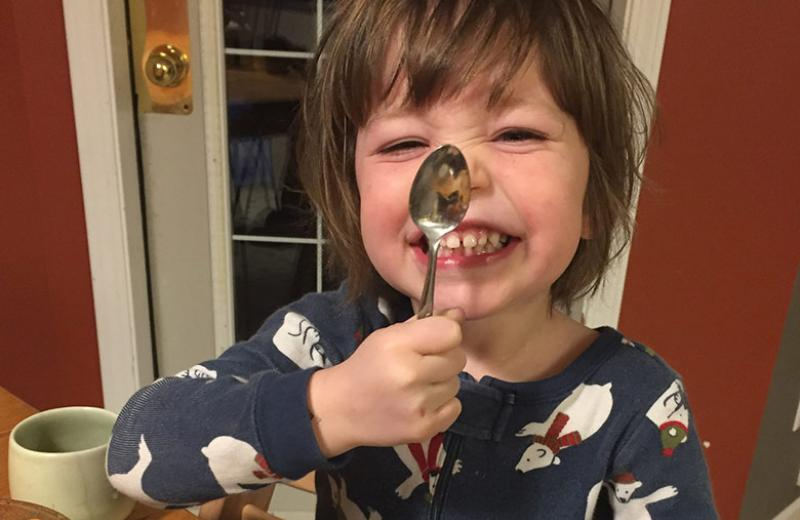 A young, smiling boy wearing polar bear pyjamas and sitting at a kitchen table holds a spoon up to his nose.