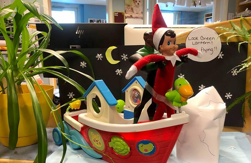 The elf on the shelf is held up by a toy version of the super hero Green Lantern, reenacting a scene from the movie Titanic.