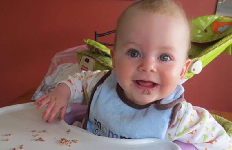 Baby eating solid foods in high chair.