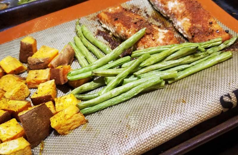 A sheet pan of cooked yams, green beans, and salmon.