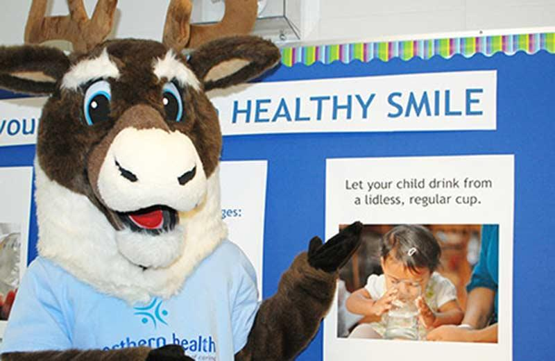 Caribou mascot in front of oral health poster.