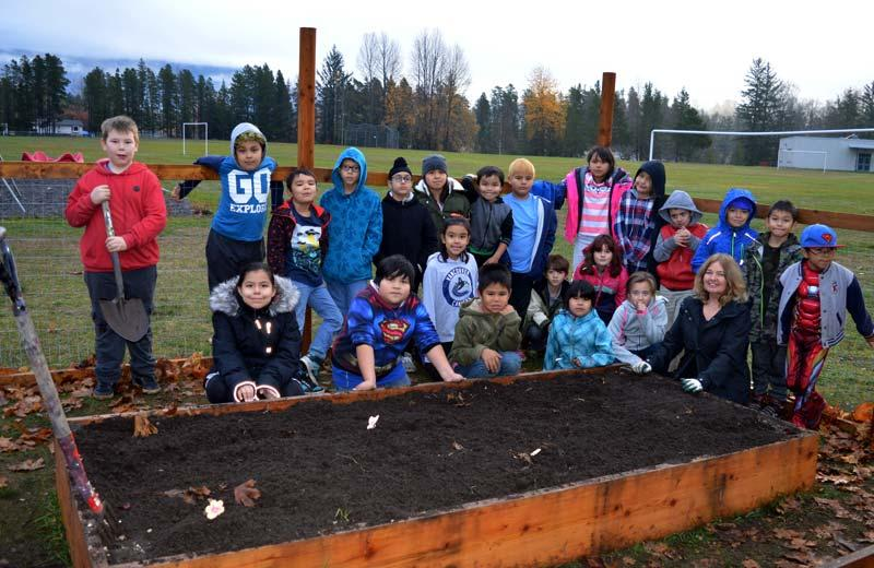 Elementary school children, some holding gardening tools, and a teacher stand in front of a planter box.