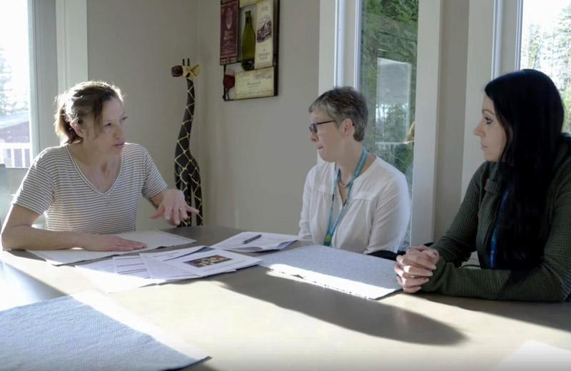Three women sit around a table discussing care.