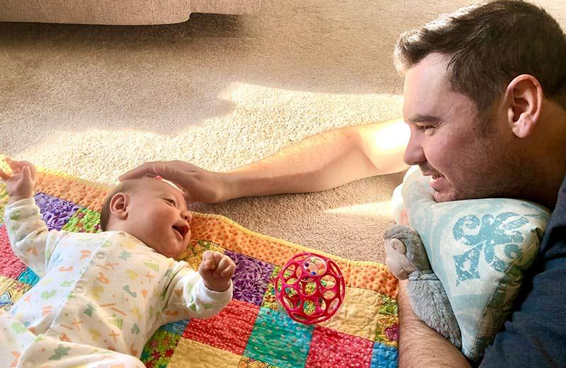 A baby lays on a quilt on the floor, smiling up at its father who looks down and smiles back.