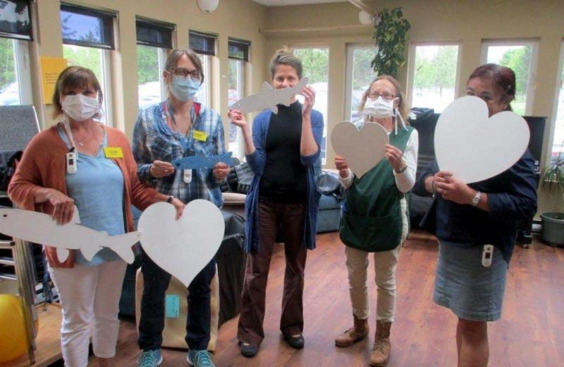 Five women stand next to each other, several wearing masks, holding cut out hearts and fish.