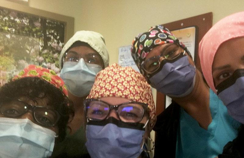 Five health care workers wearing masks and caps look into the camera.