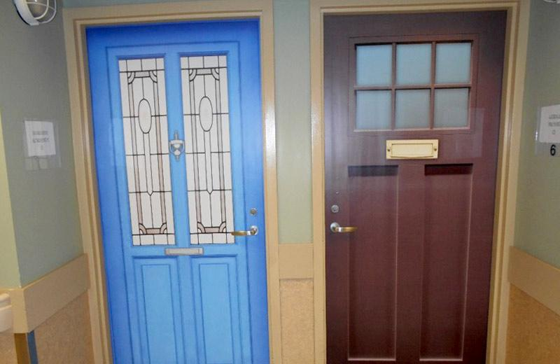 Two doors with different fake veneers. One is bright blue with long vertical windows. The other is brown with six small square windows near the top.