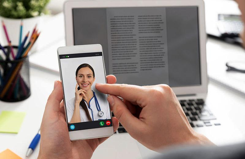 A female doctor is on a video call on a phone.