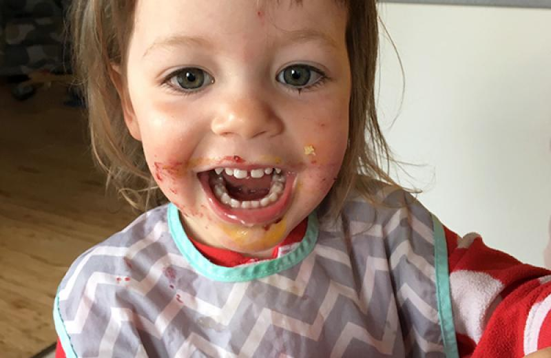 An adorable child, with food all over it's face, smiles into the camera and holds a peanut butter and jam sandwich.