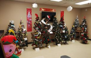 A line up of small, decorated Christmas trees in a large room decorated for Christmas.