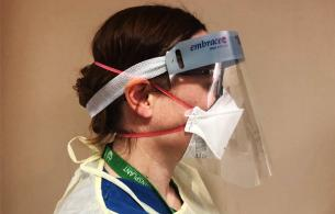 A side view of a nurse wearing a face mask and gown.