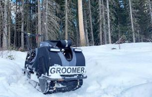 A trailer groomer sits on snow in a forest.