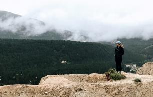 A woman stands at the edge of a cliff, forested mountains touching clouds in the background.