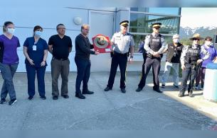 A group of health care staff and RCMP line up, with a man in the middle holding up a plaque with a hat on its front.