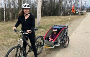 A woman rides a bike that's towing a child in a trailer.
