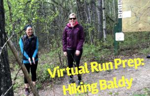 Two women in hiking apparel smile into the camera as they hike a wooded trail.