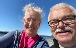 A man and woman on a rocky beach smile into the camera, blue sky and water behind them.