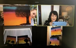 On a video chat, three youth hold up paintings while another person takes a picture.