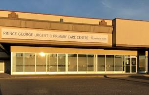 A one-story clinic that is part of a strip mall at sunset.
