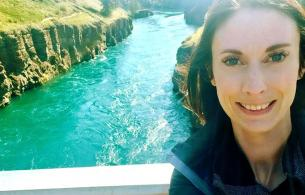 Smiling woman taking a selfie on a bridge with a beautiful teal river behind her.