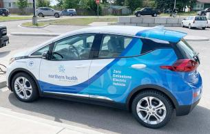 A Chevrolet Bolt with Northern Health decals is parked at a charging station.