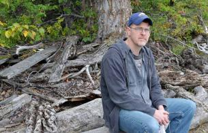 A man sits on a log and looks into the camera.