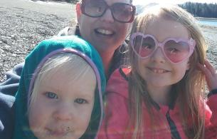 A woman in sunglasses and two children taking a selfie on a beach.