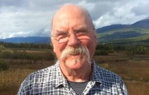 Elderly man with glasses and a large moustache stands in field with mountains in the background