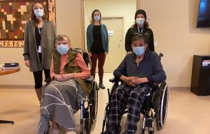 Three nurse immunizers stand behind two long-term care residents in wheelchairs.