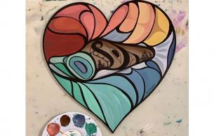 A colourfully painted wooden heart with Indigenous images on it.