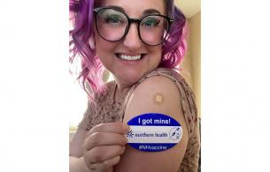 Woman shows off a sticker that says she got her vaccine