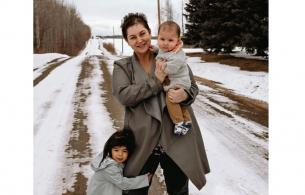 Woman holds baby on snowy country road while another child holds onto her leg